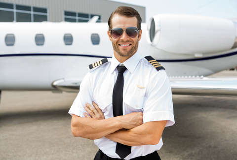 Handsome pilot standing in front of plane