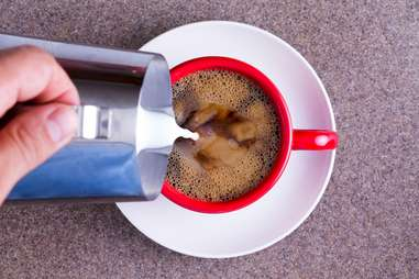 milk being poured into coffee mug whole milks creamer creamy