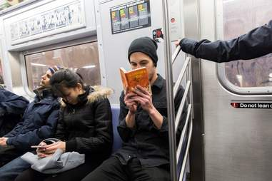 guy reading catcher in the rye on subway