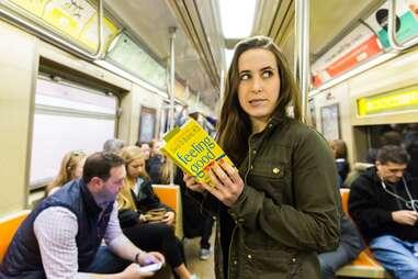 girl reading self help book on subway