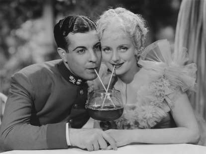 Vintage photo of couple on dating sharing drink