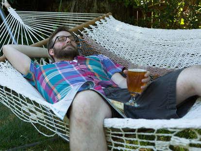 man in hammock with beer
