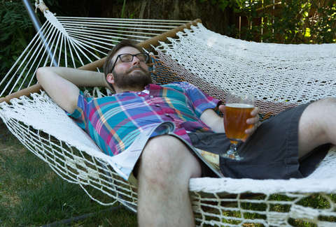 man in hammock with beer