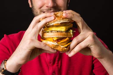 man eating big hamburger