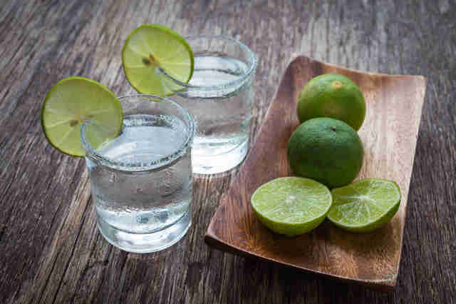 Tequila with lemon on wooden table