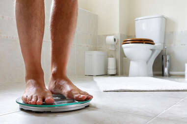 man standing on scale in bathroom