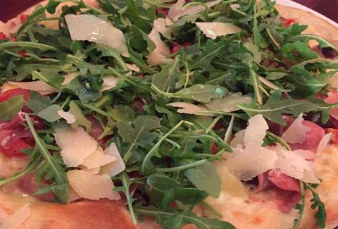 Arugula, prosciutto, and cherry tomato pizza