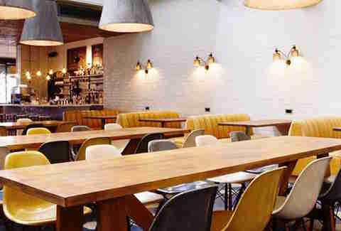 the hoxton hotel london thrillist interior long tables yellow decor