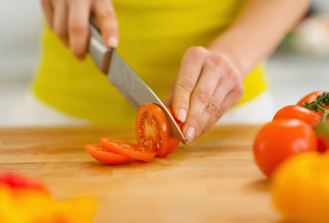 woman cutting tomatoes with a chef's knife