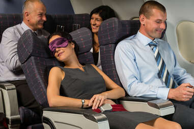woman sleeping on plane with face mask