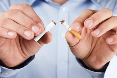 Smoker breaking cigarette