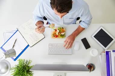 Man eating salad at work