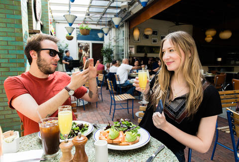 Couple taking photos of each other at brunch