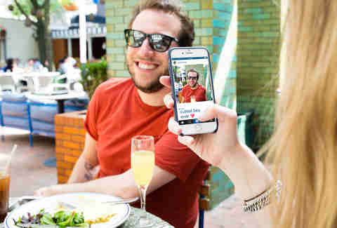 Guy having his picture taken at brunch by girlfriend