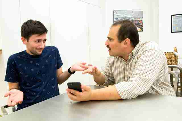man with iphone scolding other man