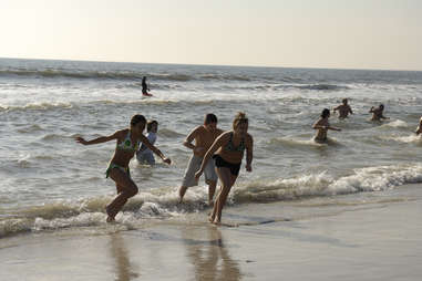 Kids joyfully running away from wave
