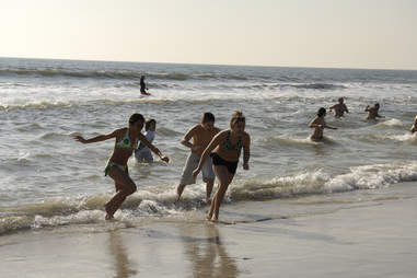 Kids joyfully running away from wave