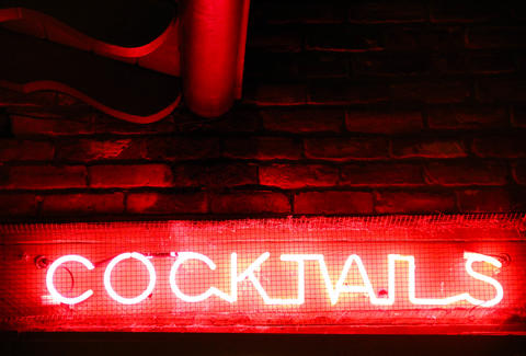 A red neon sign advertising cocktails.