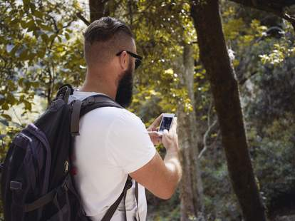 Man on iPhone in nature