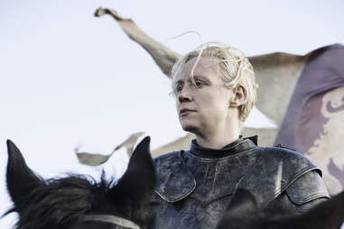 Gwendolyn Christie as Brienne of Tarth in front of Lannister banners