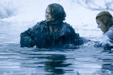Alfie Allen as Theon Greyjoy and Sophie Turner wading through a river