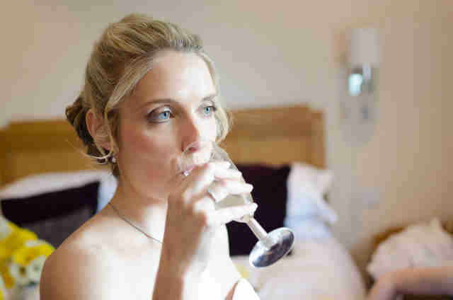 A bride takes a sip of champagne