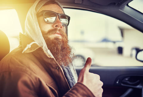 hipster man in car giving thumbs up