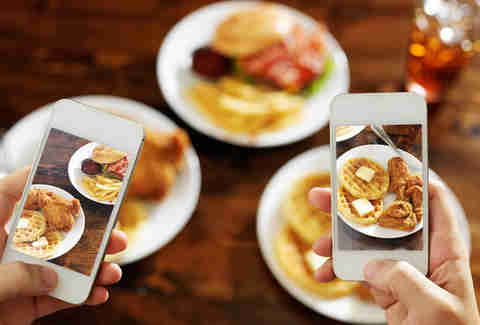 Food bloggers taking a picture of food with smartphones