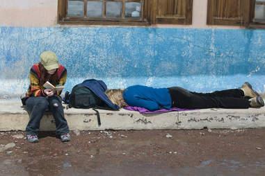 tourist sleeping on the sidewalk