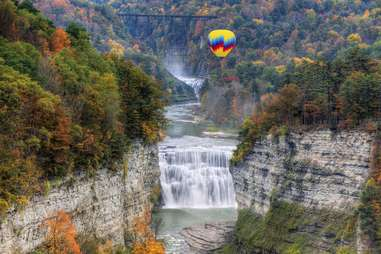 a hot air balloon over a large forest waterfall