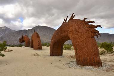 a dragon sculpture diving in and out of the sand in the desert