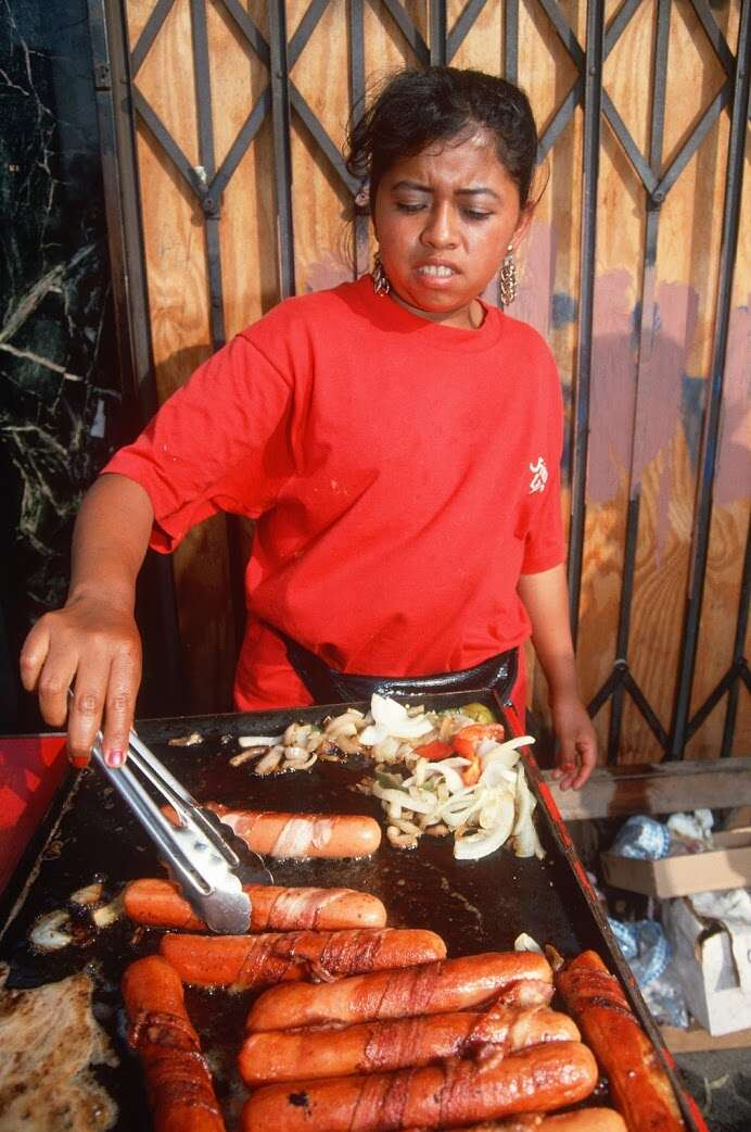 Woman grilling bacon-wrapped hot dogs
