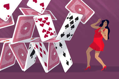 stack of cards falling on woman