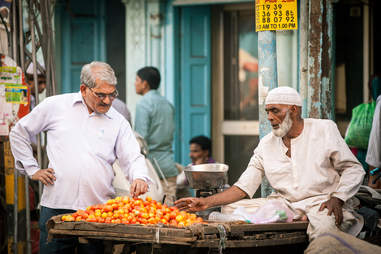 Man buying tomatoes in Indian marketplace