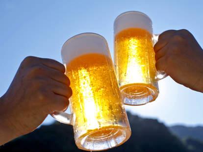 Two people cheers their beers