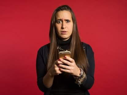 Woman looking anxious looking at iPhone