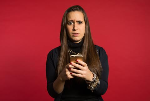 Woman looking anxious looking at iPhone