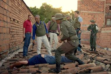 U.S. Drug Enforcement Agency (DEA) Officers stand over Pablo Escobar's dead body after years of chasing the elusive drug trafficker.