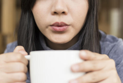 woman blowing on hot coffee