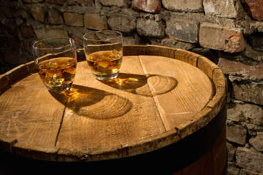 Glasses of whiskey on a barrel