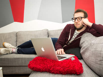 bored man on sofa with laptop