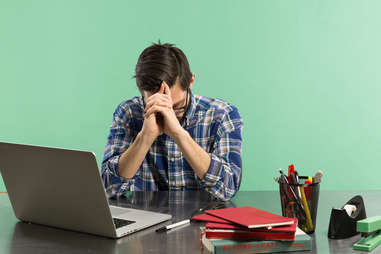 man bored at his office work desk