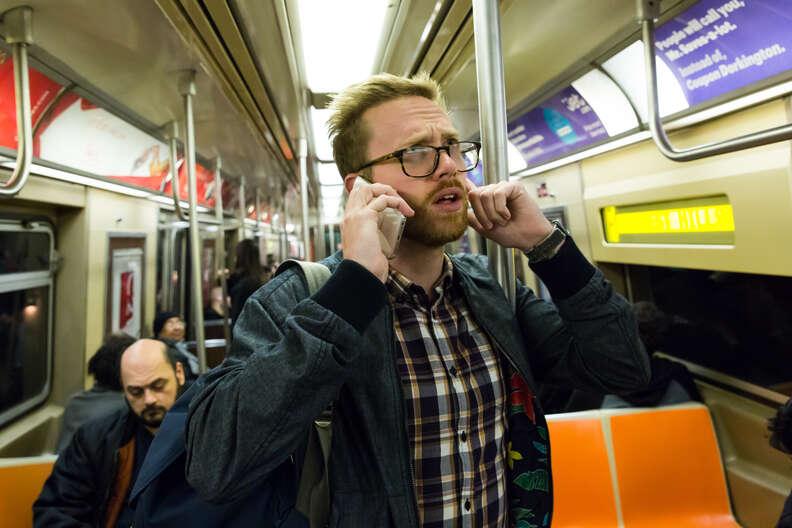 man talking on phone on subway car