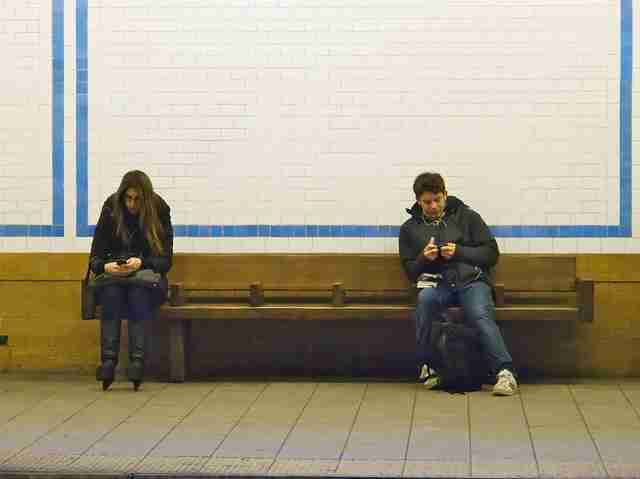 two people using cell phones at subway station