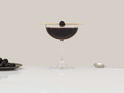 Black Manhattan cocktail in a coupe glass