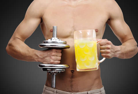 guy holding beer and dumbbell