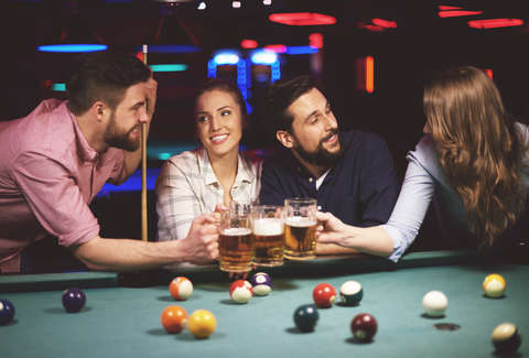 Friends drinking beer while playing pool