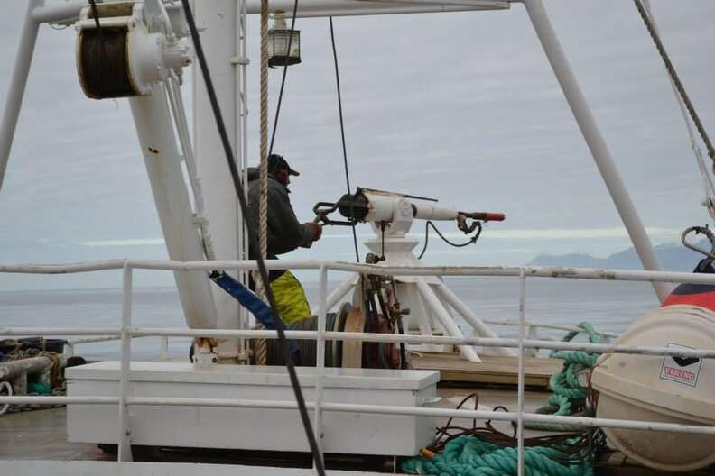 A Norwegian whale hunter standing behind a harpoon on a whaling ship