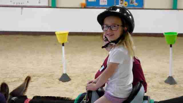 Girl riding therapy donkey at The Donkey Sanctuary in Birmingham