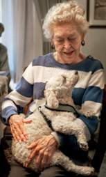 Elderly woman hugging dog
